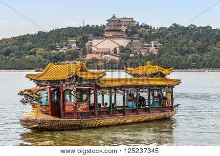 Beijing China - October 14 2013: Tourists on a dragon boat floating on the Kunming Lake Beijing China. Summer Palace in the background..