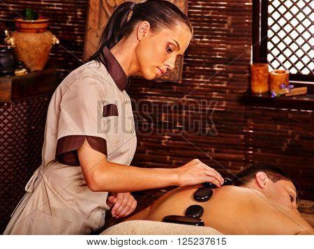 Man having oil massage hot stones Ayurveda spa treatment.