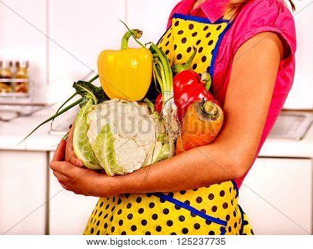 Child holding vegetables at kitchen. Close-up of hands holding vegetables.