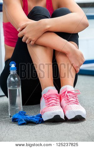 Girl in a pink tank top is sitting on the floor, wrapped her arms around her knees. A bottle of water in the foreground. Close-up of female legs.
