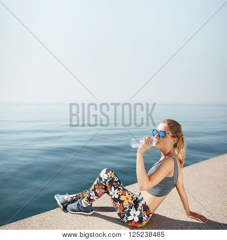 Young Female Jogger Drinking Water Sitting On The Beach After Hard Running Work Out Drinking Water O
