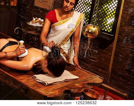 Woman making ayurvedic massage the patient back with a bag of rice. Indian SPA. Decorated with bamboo.