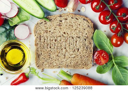 Slice of a whole wheat bread and healthy organic vegetables for making sandwiches. Healthy eating or cooking concept.
