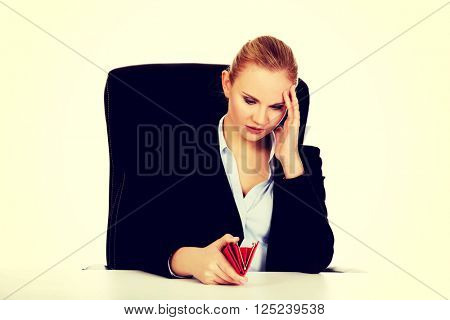 Worried business woman sitting behind the desk with empty wallet