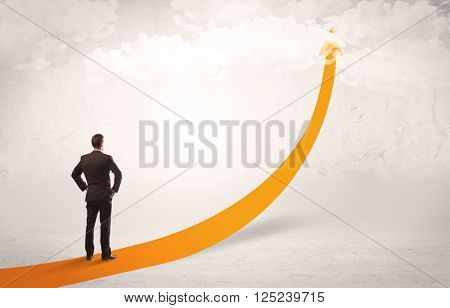 A young adult salesman standing on a big orange arrow pointing up in a bright empty space concept