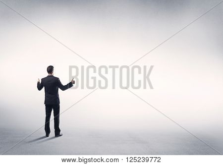 Corporate business male in modern suit standing in big blank empty grey space concept