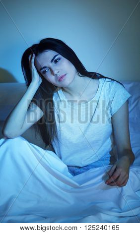 Young woman sitting with terrible headache in bed at night