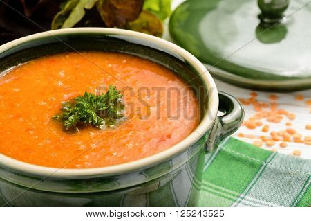 Red lentil cream soup on wooden table.