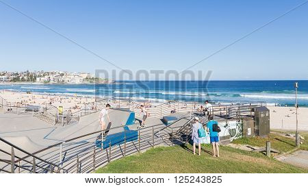 Sydney - March 1 2016: beautiful Sate Park with interesting slides and skateboarders ride in the beautiful city beach and people sunbathing by the sea March 1 2016 Sydney Australia