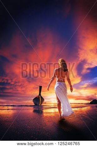 Young woman in white trousers walking alone on the beach with long tail boat on background