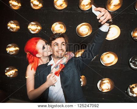 Happy couple in nightclub do selfie on mobile phone. Young redheaded girl with big tattoo hugs young laughing men. Party selfie of boyfriend and girlfriend on black background.