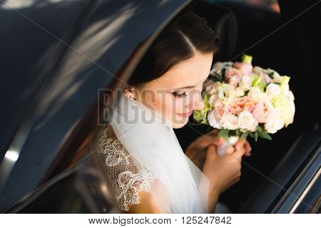 Close-up portrait of a pretty bride in a car window.