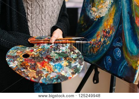 Closeup of paintbrushes and stained mixing  palette in woman hands. Unrecognizable female artist in a workshop holding a stained palette and brush. Closeup of painting tools