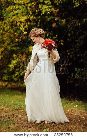 Portrait of magical beautiful young blonde bride in elegant dress with bouquet of red flowers in the park