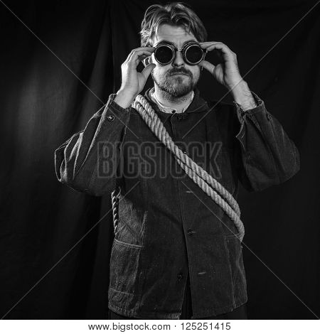 Working in a black robe corrects welding goggles . black background