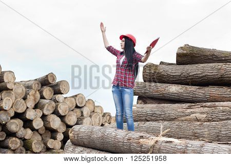 Female Forestry Engineer Beside Logs