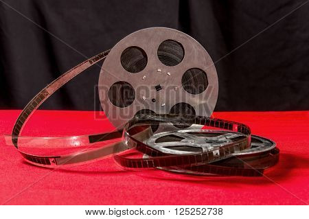 reel of film on a red table with black background
