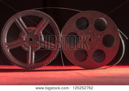 reel of film standing on a red table with black background