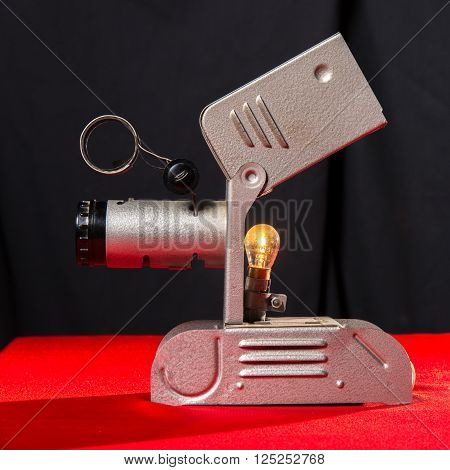 vintage movie spotlight on red table and black background