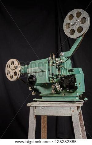 Worm's eye view of a retro movie projector on a black background