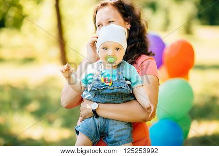 Young family with kids having picnic with pillows and colored balloons outdoors. Parents with two children relax in a sunny summer garden. Mother father little girl and baby boy playing in park.