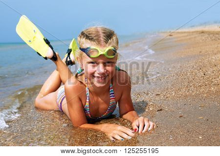 Happy little child smiling on summer beach sand with snorkel equipment looking to side at copy space after swimming with fins and mask on vacation.