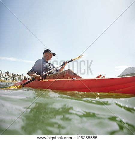 Man Kayaking On Lake In Summer