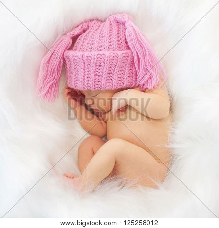Sleeping newborn baby in the white fur. Birth concept.
