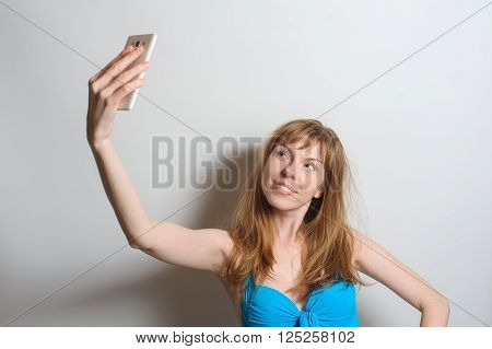 Positive young woman with freckles playing with hair and taking selfie. Joyful beautiful redhead woman without makeup smiling happily at camera, wearing blue swimsuit. White background.