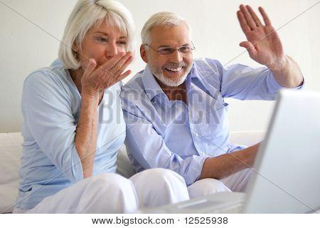 Senior couple waiving at webwam