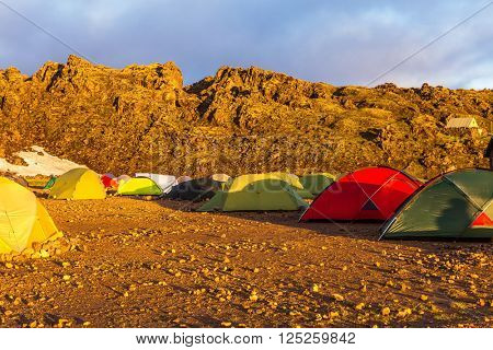 Tents tourists, mountains and glaciers covered with warm sunlight. Fairy dawn National Park Landmannalaugar, Iceland