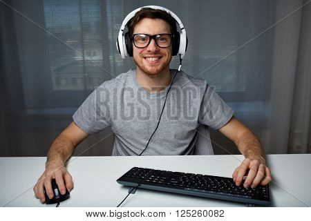 technology, gaming, entertainment, let's play and people concept - happy smiling young man in eyeglasses with headset playing computer game at home and streaming playthrough or walkthrough video
