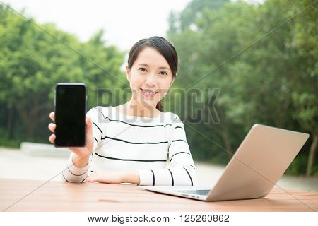 Woman with laptop computer and show with the blank screen of cellphone
