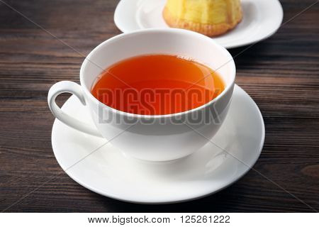 Hot black tea in a cup on wooden background