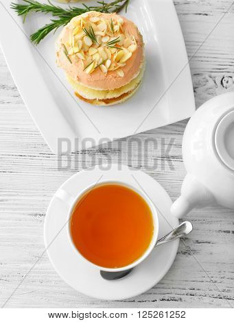 Tea with cakes on wooden background, top view