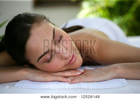 Beautiful woman on a massage bed with hot stones