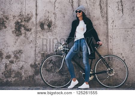 That was great ride! Beautiful young woman holding hands on her bicycle and looking away with smile while standing against concrete wall outdoors