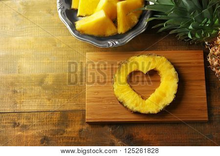 Juicy pineapple slice with cut out heart shape on wooden cutting board