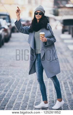 Hey taxi! Full length of beautiful young woman holding coffee cup and waving for taxi while standing outdoors