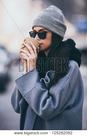 Sip of fresh coffee. Portrait of beautiful young woman drinking coffee and looking away while standing outdoors