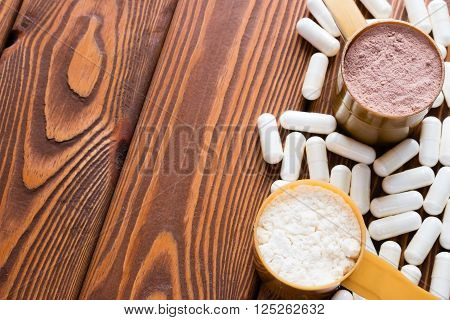Capsules Of Creatine And Protein Measuring Spoons Closeup