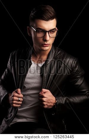 portrait of dark haired macho man in black leather jacket and white shirt wearing glasses while pulling his jacket and looking away from the camera in isolated black studio background