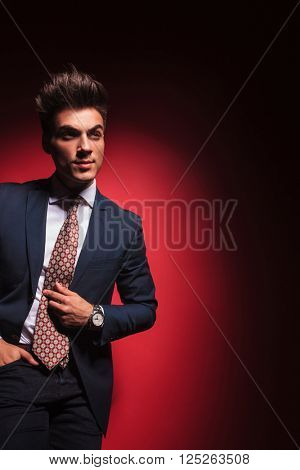 smart casual young businessman in black with red tie posing standing in red studio background with hand in pocket fixing his tie while looking away from the camera