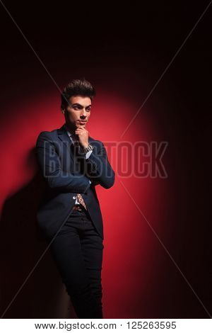 portrait of standing pensive businessman in black with hands and legs crossed posing in red studio background while looking away from the camera