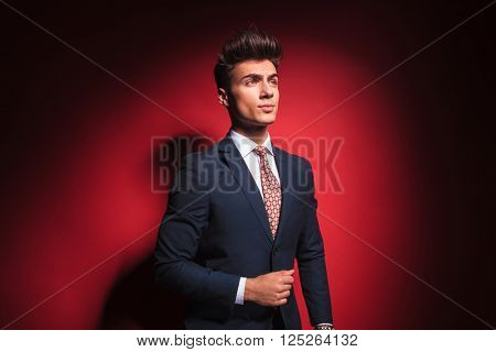 portrait of confident young businessman in black suit with red tie posing arranging his jacket and looking away from the camera in red studio background