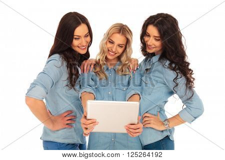 three smiling casual women looking at the screen of a tablet pad computer on white background