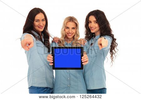 three happy casual women presenting a tablet's screen and pointing the fingers to you on white background