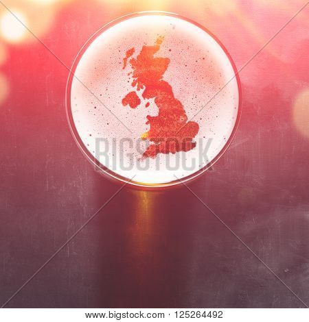 English beer concept, Great Britain silhouette on foam in beer glass on black table, view from above