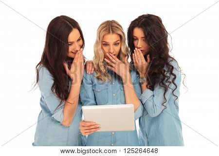 three women using a tablet pad computer are shocked of what they are seing , on white studio background
