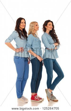 full body picture of 3 casual women standing in line and looking up to something  on white studio background